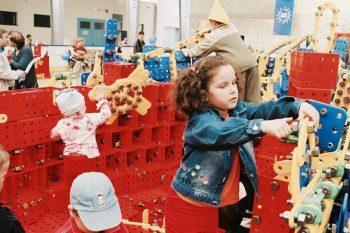 Die Kinder bauen gemeinsam ein großes Schiff aus Bausteinen.